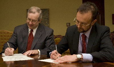 U.S. Embassy Deputy Chief of Mission Richard LeBaron (left) and Mark Higson of the Department of Business Enterprise and Regulatory Reform sign the memorandum of understanding.